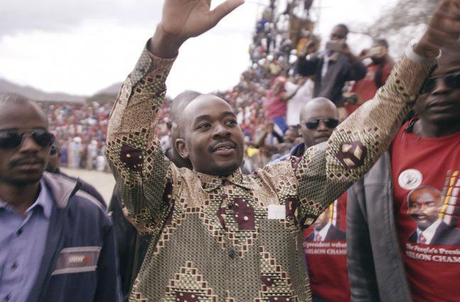 A man with Black skin and a patterned shirt addresses a large crowd.