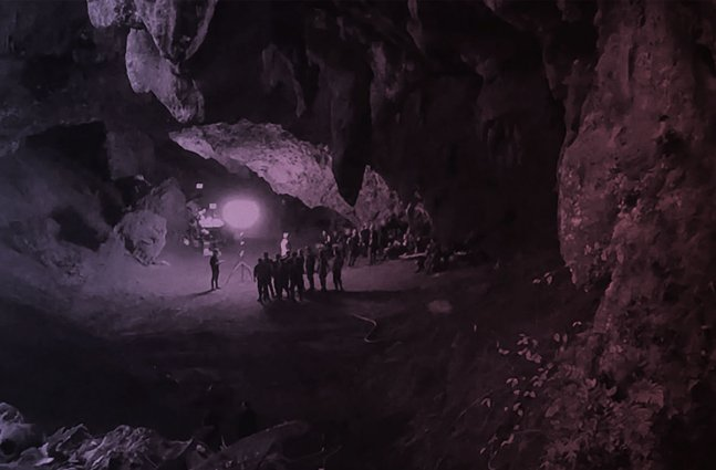 Several people inside a dark cave.