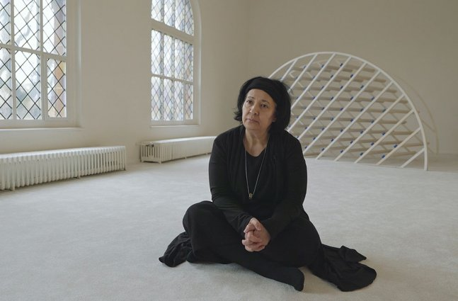 An older woman with brown skin and black hair wearing a black outfit sits on the floor.