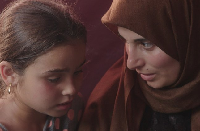 A woman in a brown hijab talks to a little girl.