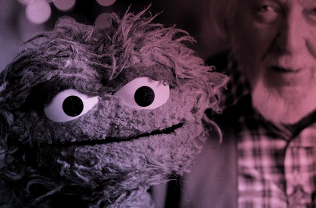 An older white man with gray hair holds up a green, scraggly puppet.