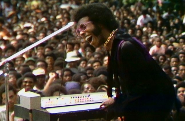 A Black man with black hair wearing pink glasses, a gold necklace and a purple suit. He is playing keyboard to a crowd.
