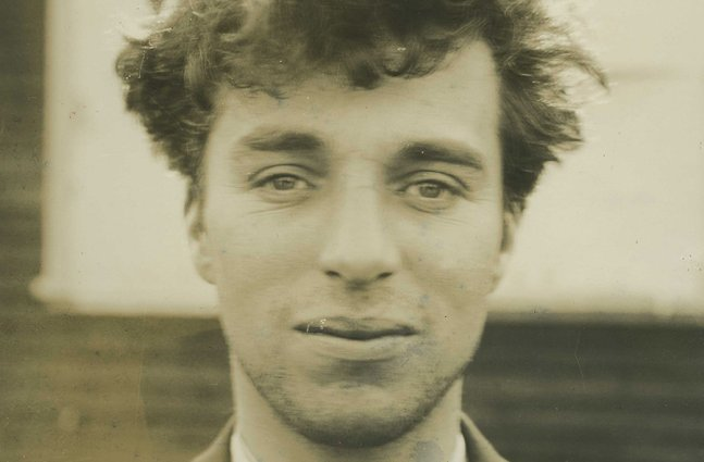 A sepia portrait of a white man with curly light hair.