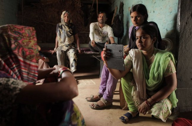 A group of people with brown skin sit in a room. Two women in the front film someone off screen with their phone.