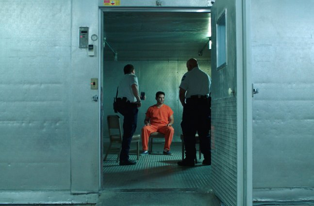 A man in orange jumpsuit is being interrogated by officers