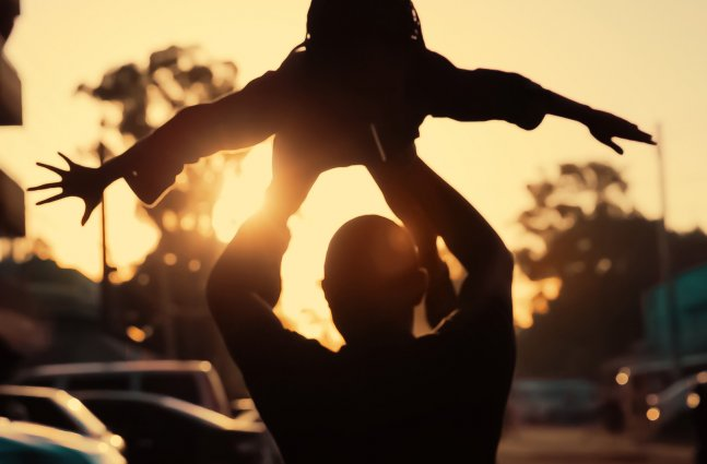 A man is lifting up a child against sunset