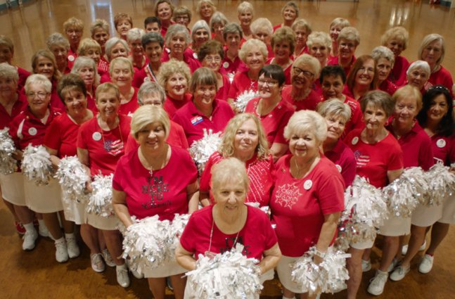 An elderly cheerleading team, all wearing red tshirts and white skirts