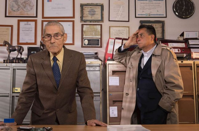 An elderly man in a brown suit and a middle-aged man in trench coat are behind an office desk