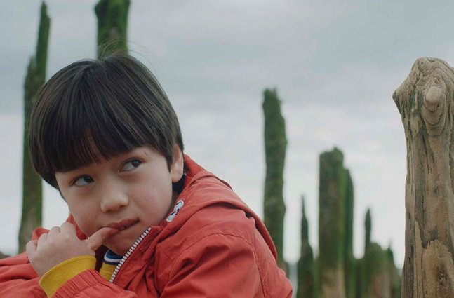 A young boy in an orange coat looking to the side