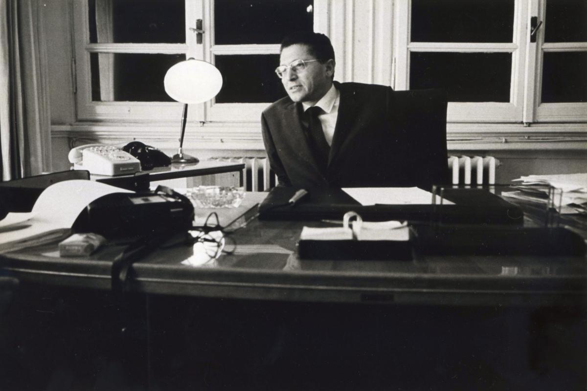Kikhia leans over his mid-20th century style desk