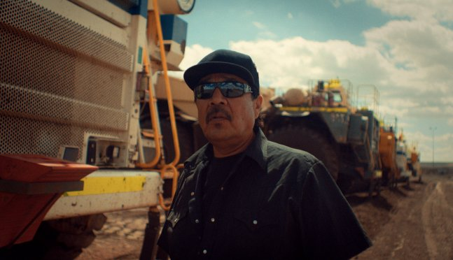 Indigenous coal miner poses for photo in front of plant equiptment