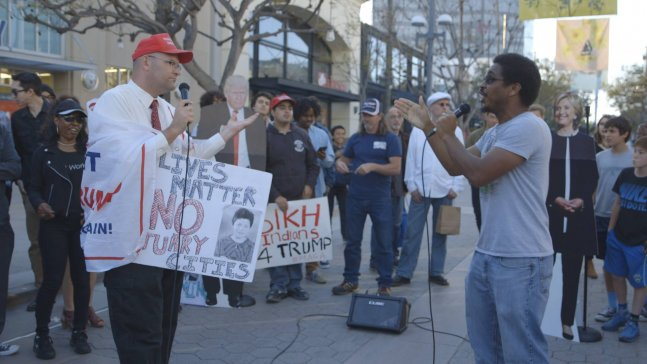 A Trump supporter wrapped in a MAGA flag debates with an opponent in front of a crowd on the street