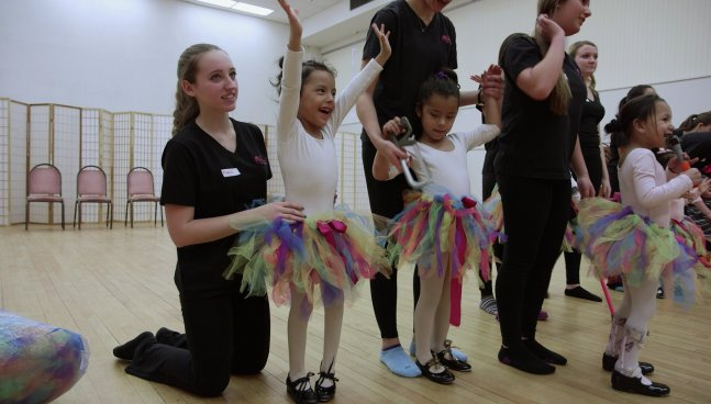 Three female children in pink leotards and rainbow-colored tutus stand before adult female volunteers dressed in black.