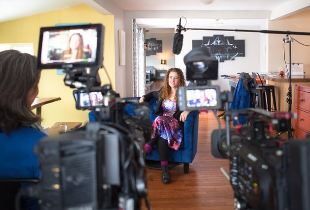 Woman in a galaxy-themed dress sits in an interview set up before a documentary crew
