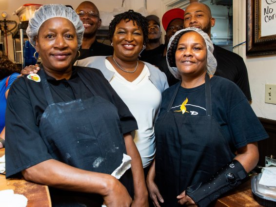 Group of African-American is smiling at the camera in a kitchen.