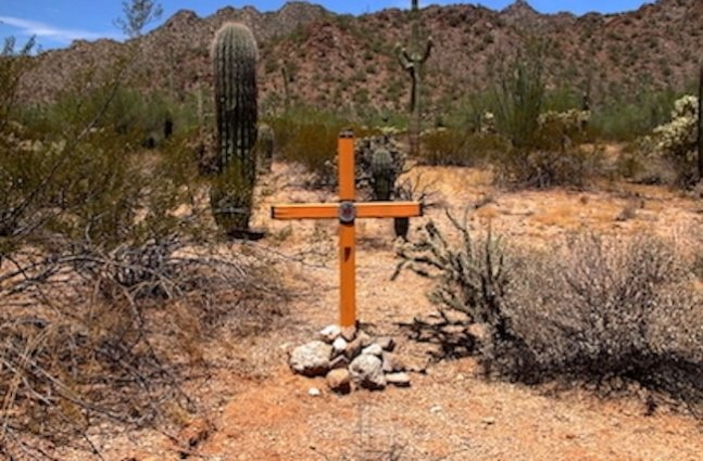 An artistic orange cross propped up with stones in the Sonoran Desert