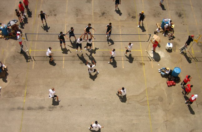 We look down from above at a  crowd of Asian-American men playing street volleyball.