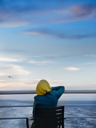 An individual in a yellow hijab sits in a chair in the stern of a boat before the ocean