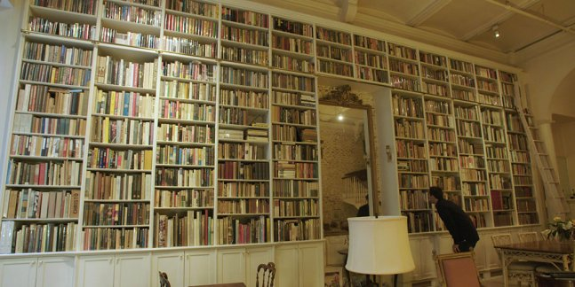 One person examines a book in the stuffed personal bookshelf of someone's home.