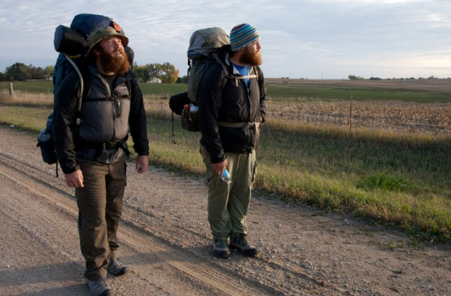two veterans pause in the middle of road amid their backpacking trip
