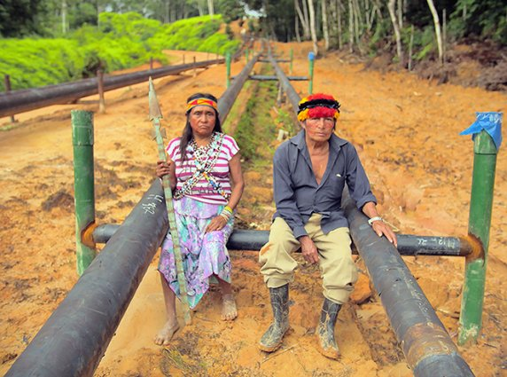 Two indigenous people sitting on black pipes in the Amazonian forest.
