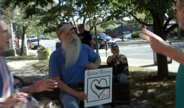 A white man with a beard holds an anti-refugee sign in a residential neighborhood.