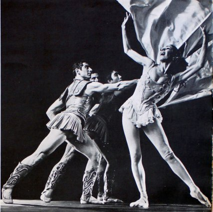 Three White male ballet dancers in Roman Empire guard outfits dance behind a White female ballerina