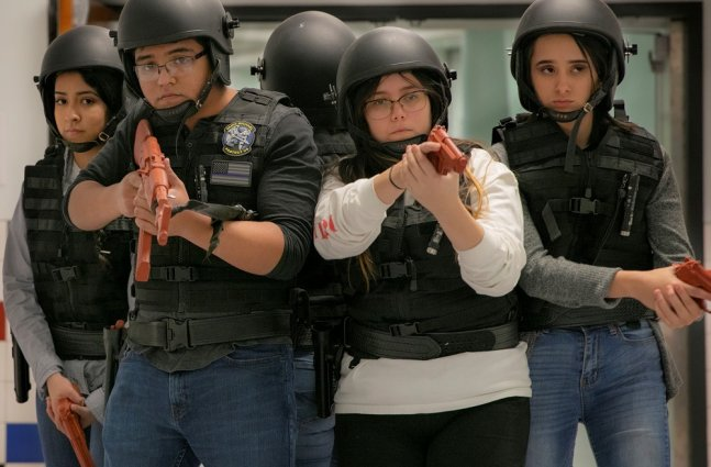 A group of high school students are in training, wearing tactical vest, helmets and fake guns