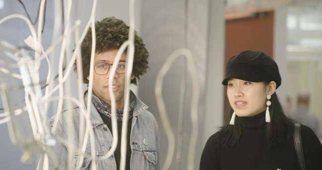 A young Black man with curly hair, glasses and a scarf and a young Asian woman with a black cap and white earrings stand before an abstract white curly art piece in a museum.