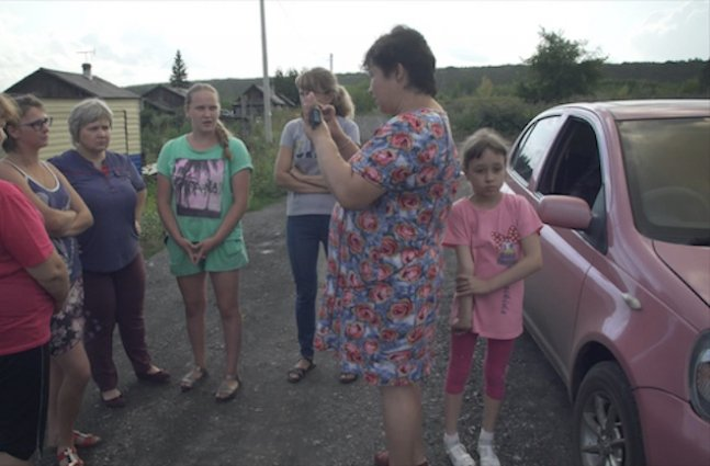 Homemaker-turned-journalist Natalia Zubkova in a blue and pink flowered dress, interviews five women with her cell phone in a rural village as her young daughter, in pink shirt and capri pants, waits nearby.