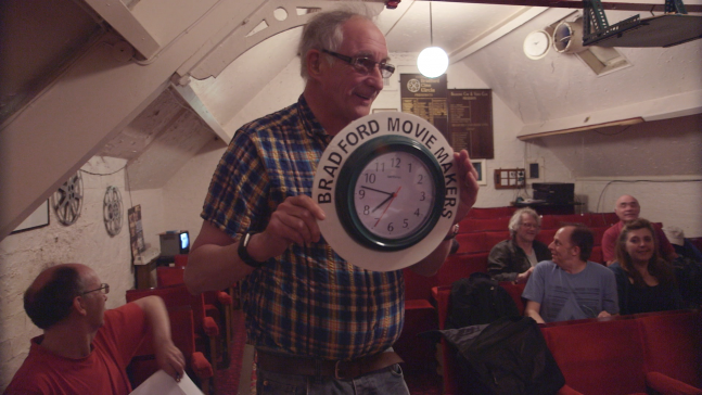 A man holding green clock that is labeled 'Bradford Movie Makers'
