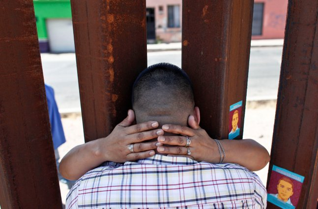 image of two people embracing eachother through the U.S/Mexico border wall