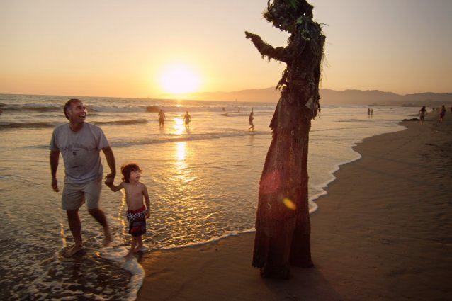 Person in tree costume waving at a child on a beach