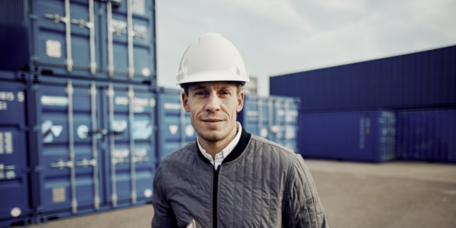 A port worker standing in front of several blue ship crates.