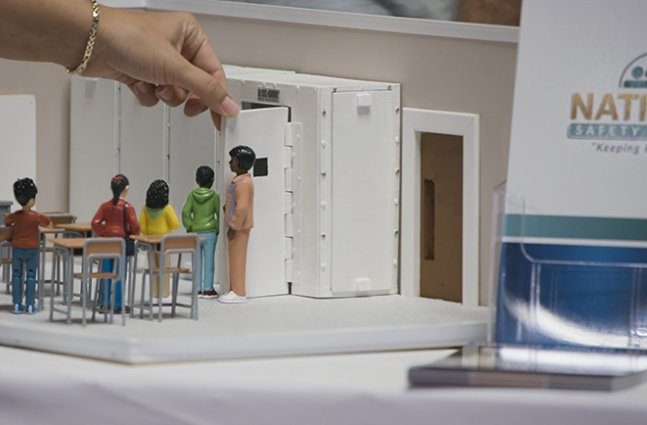 hand of person uses small replica of school classroom to teach gun related safety protocols