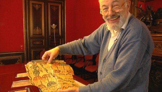 A Caucasian man is holding up an ancient scroll while smiling.