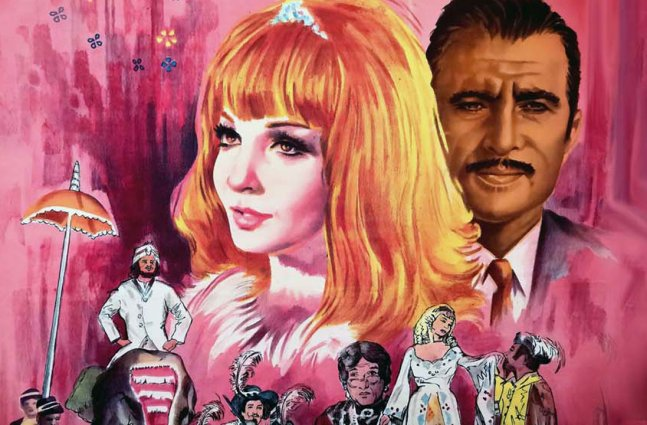 An elaborate pink painted film poster featuring a White women with vibrant red hair next to an Egyptian man with a mustache. Several other, smaller painted people adorn the bottom of the poster.