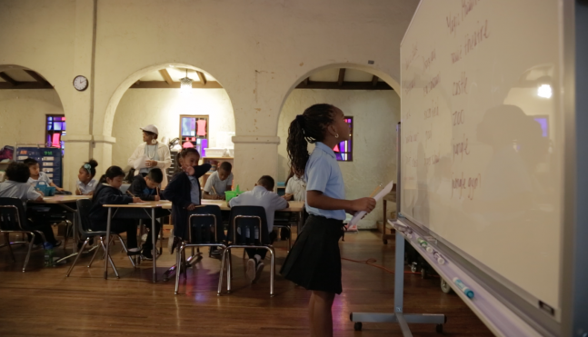 a grade school African American girl in a school uniform looks up at a white board with a paper in her hand in front of the rest of her young classmates.