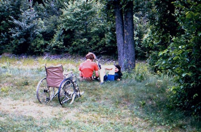 two camp members sit under a tree while attending a disabled persons camp; a wheel chair is focal point of image