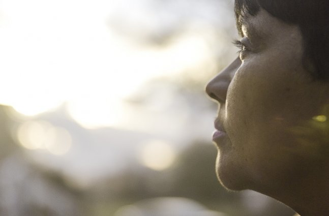 """A still from """"Commuted"""": Protagonist Danielle Metz, a middle aged woman, is shown in sharp focus in the foreground, looking out at a sunset."""