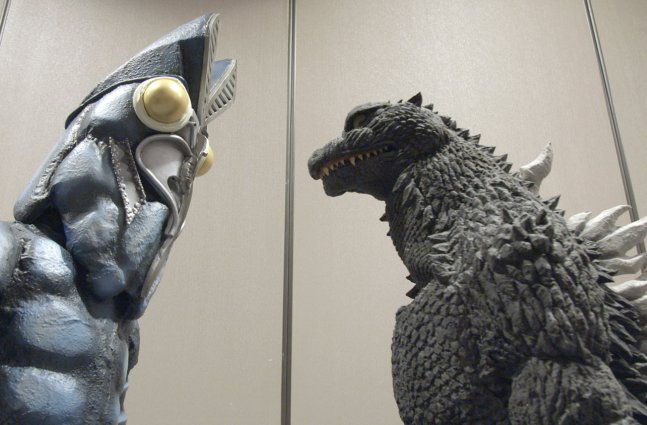 two people in Godzilla costumes stare at each other
