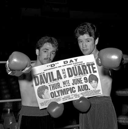 Black and white photo of two boxers holding a newspaper