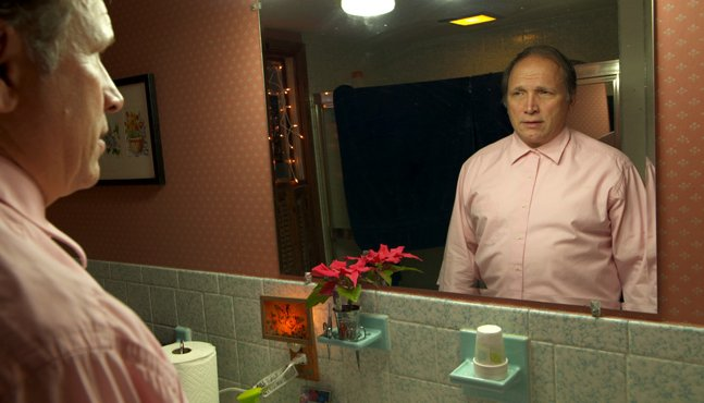 white middle aged male stares at himself in the bathroom mirror wearing pink button up