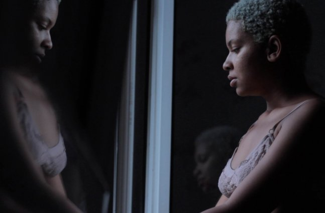 An African-American female looking at herself through the mirror.