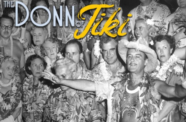 "A black and white photo of a large group of middle-aged and older partygoers with ""tiki"" style clothing, a man in the center holds out his arms wide."