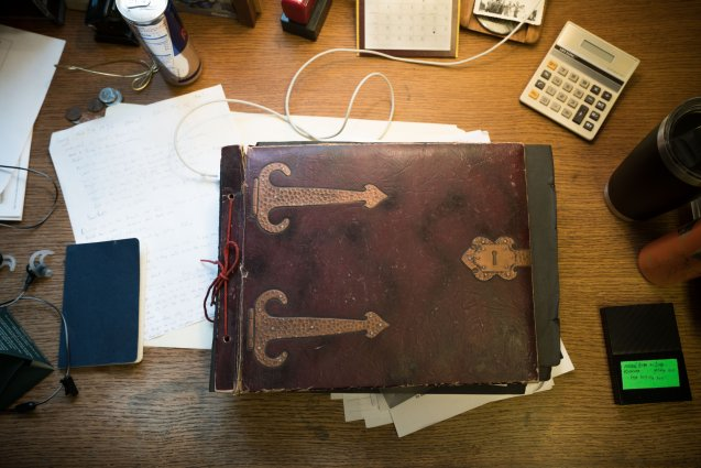 A rustic old notebook of archived documents sits on a desk surrounded by smaller papers and notepads.