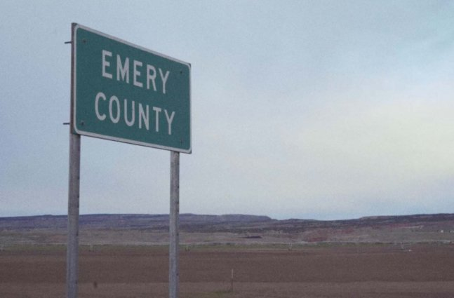 """A large empty vista with a single green highway sign reading """"Emery County"""""""