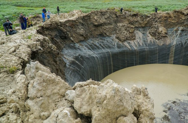 group of people stare into sink hole cause by underground methane explosions