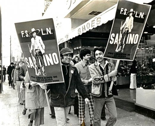 Black and white photo of protesters holding a F.S.L.N. poster.