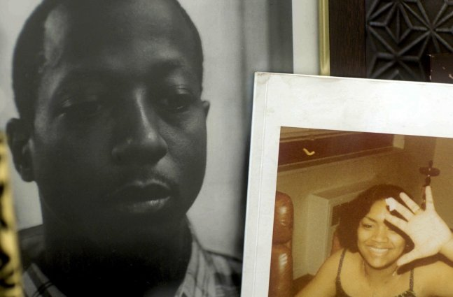 """A still from """"For Venida, For Kalief"""": Two framed photos sit on a bedside cabinet, one of Kalief Browder, a young Black man wearing a checked shirt, and the other of a young Black woman wearing a sleeveless black top."""